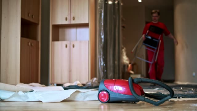 mogen man rengöra golvet med dammsugaren - endast en medelålders man bildbanksvideor och videomaterial från bakom kulisserna