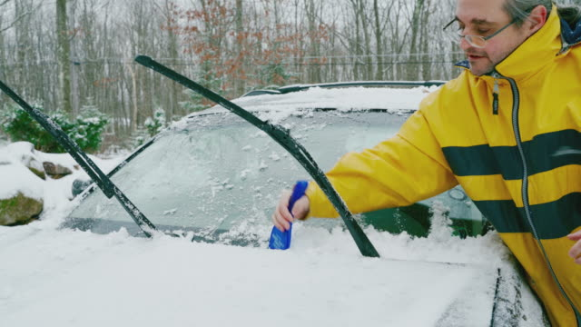 Mature man cleaning windshield wipers blades from snow and ice.