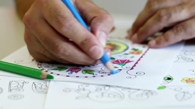 mature man coloring a coloring sketch - solo un uomo maturo video stock e b–roll