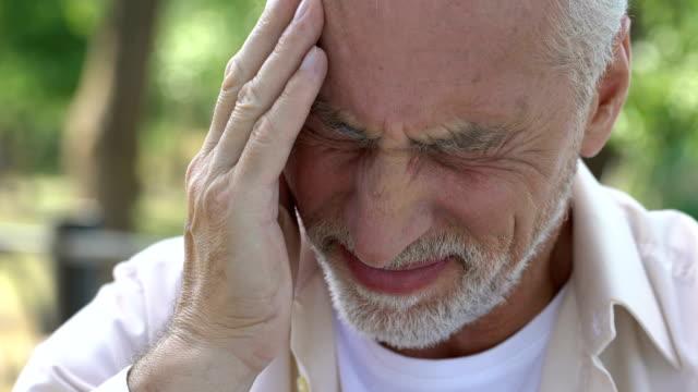 成熟した男の頭、片頭痛発作、血栓のリスクに突然鋭い痛みを感じて - 尖っている点の映像素材/bロール