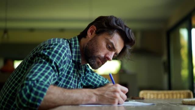 vídeos de stock e filmes b-roll de mature man filling in paperwork - carta documento