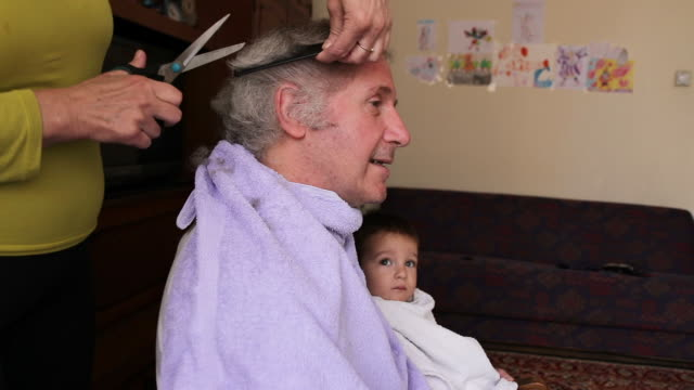 Mature man getting home haircut from his wife at home Mature, gray haired man sitting at chair and holding his grandson while his wife cutting his hair at living room during covid-19 lockdown wearing a towel stock videos & royalty-free footage