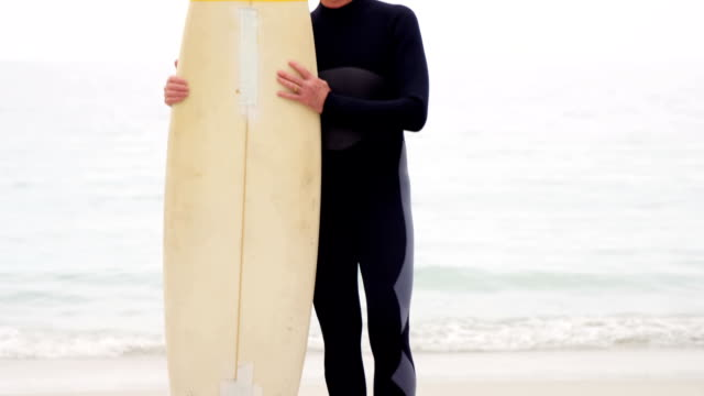 Mature man holding surfboard video