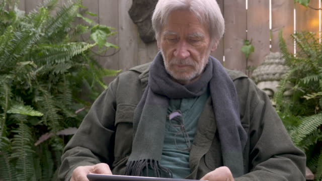 Mature man in his 70s reading a tablet on his lap in his garden video