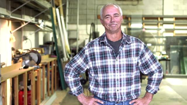 vídeos de stock e filmes b-roll de mature man in plate glass warehouse - homem casual standing sorrir