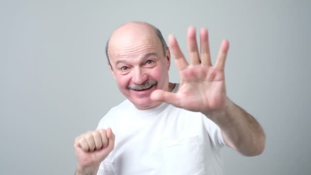 mature man in white t-shirt shows five fingers. - maglietta bianca video stock e b–roll