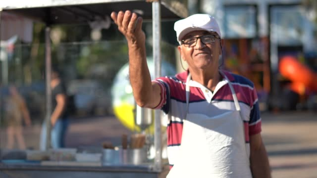 mature man inviting people to come to your churros store - cultura latino americana video stock e b–roll