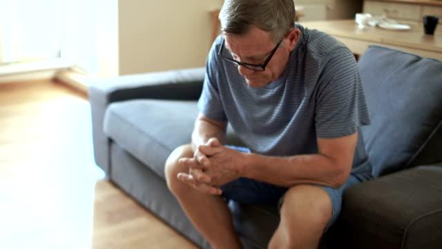 vídeos y material grabado en eventos de stock de hombre maduro es triste sentado en el sofá. soledad, problemas psicológicos, la edad de jubilación - geriatría