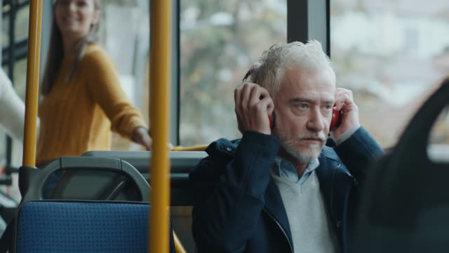 Mature man listening music on headphones in bus video