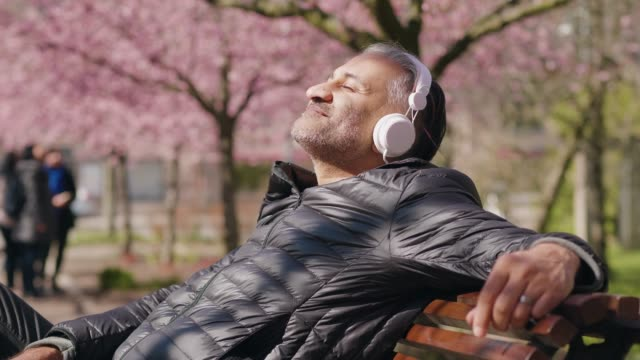 mature man listening to music in the park - садовая скамья стоковые видео и кадры b-roll