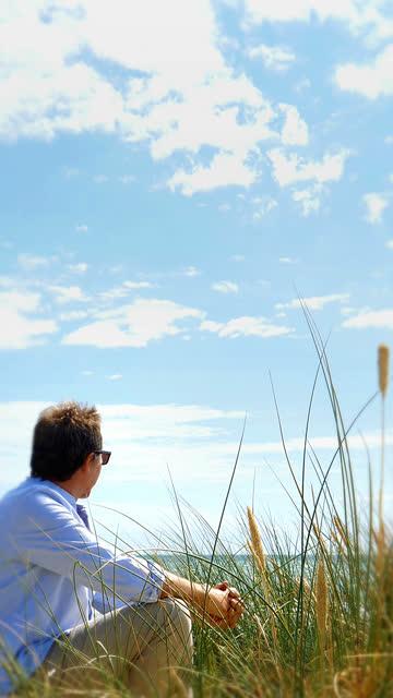 Mature man looking at horizon over sea. Vertical format.