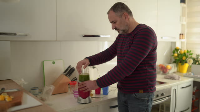 mature man making healthy smoothie - healthy green juice video stock e b–roll