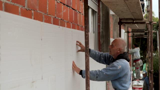 mature man placing polystyrene foam sheets on house for external wall insulation - poliuretano polimero video stock e b–roll