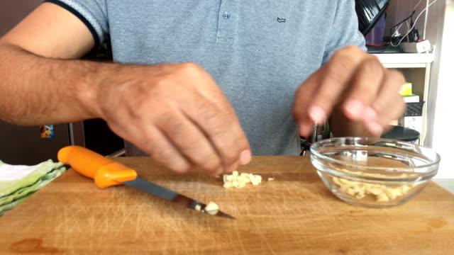 Mature Man Preparing Garlic for Frying - video