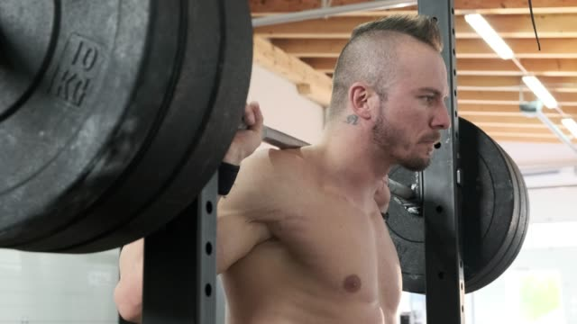 Mature man preparing to lift heavy weights at the squat rack