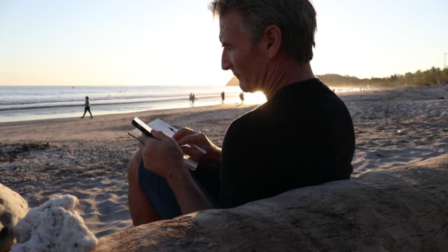 Mature man relaxes on beach at sunrise