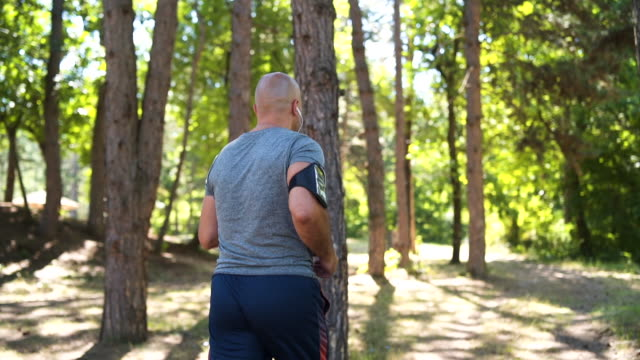 Mature man running in forest Mature man jogging, stretching in nature 50 54 years stock videos & royalty-free footage