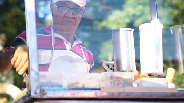 mature man selling churros at street - video di bancarella video stock e b–roll