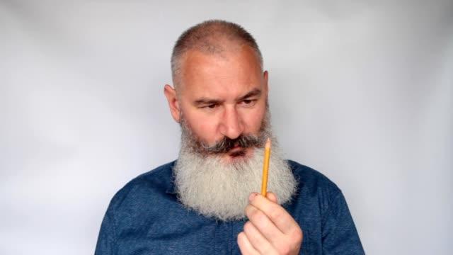 vídeos de stock, filmes e b-roll de homem maduro afia lápis com planador. engraçadas caretas do avô barbudo engraçado. retrato do homem mais velho em pano de fundo cinza. - afiado