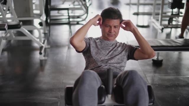 vídeos de stock e filmes b-roll de mature man sit up and exercise in fitness gym. - dureza