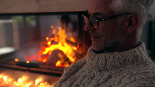 Mature man sitting by fire place in living room video