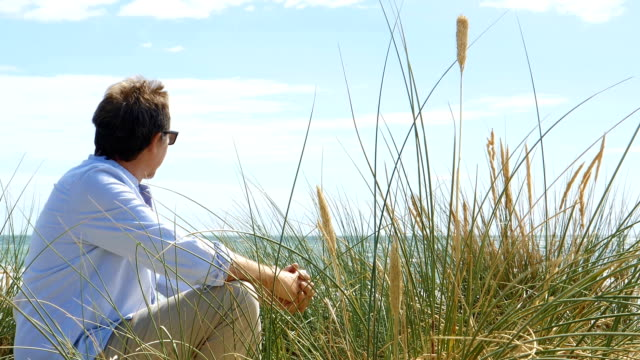 mature man sitting by sand dunes at the beach. dolly shot. - paesaggio marino video stock e b–roll