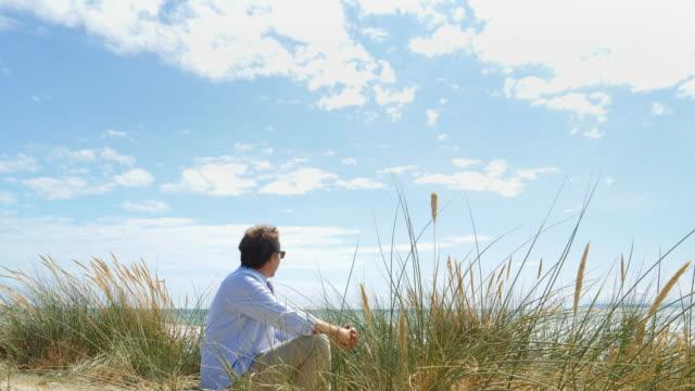 mogen man sitter av sanddynerna på stranden. - vattenlandskap bildbanksvideor och videomaterial från bakom kulisserna