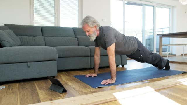 vídeos de stock e filmes b-roll de mature man stretching at home on exercise mat - treino em casa