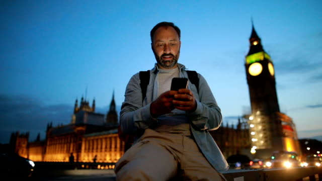 Mature man texting on the Westminster bridge video