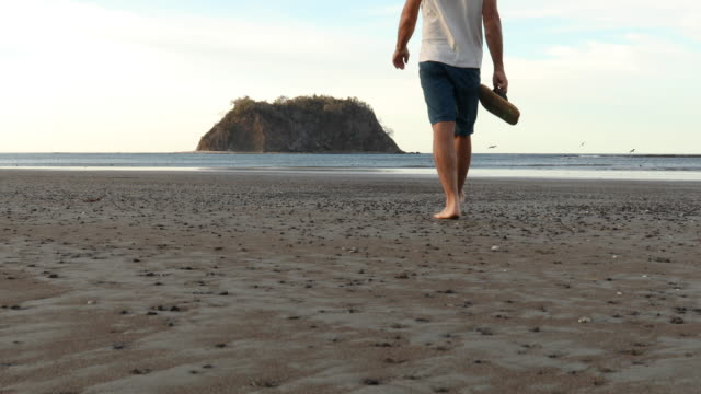 mature man traverses deserted beach at sunrise - pantaloncini video stock e b–roll