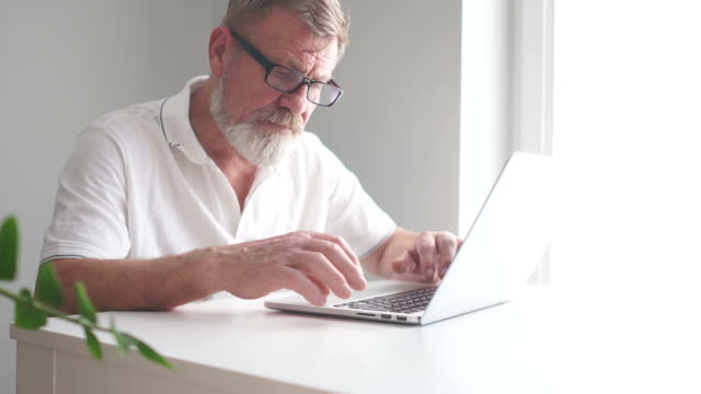 mature man using a laptop to work at home. writer or scientist at work. senior citizen writes a letter using a computer, remote employment, freelance - abbigliamento elegante video stock e b–roll