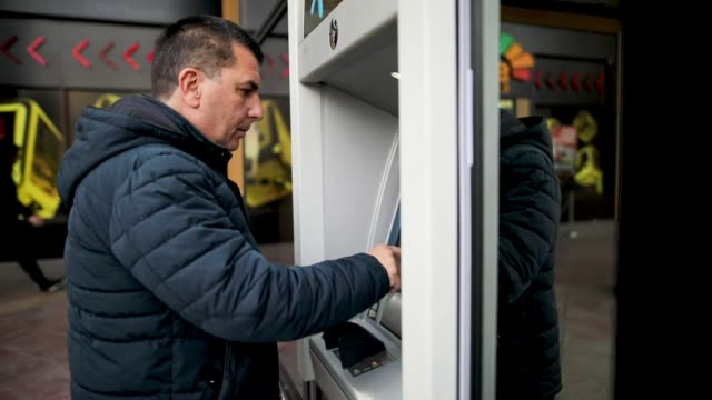 mature man using atm - banks and atms stock videos & royalty-free footage