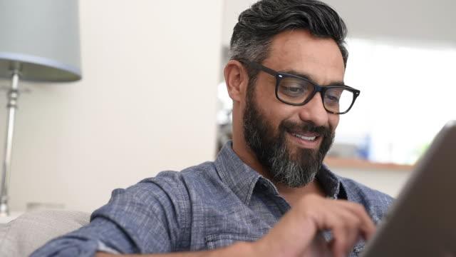 mature man using digital tablet - guy sofa video stock e b–roll