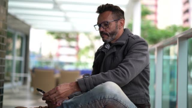 vídeos de stock, filmes e b-roll de amadurecer o homem usando o celular no escritório de casa - povo brasileiro