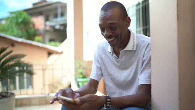 reife mann mit handy zu hause - smartphone mit corona app stock-videos und b-roll-filmmaterial