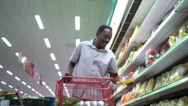 reife mann zu fuß und mit handy im supermarkt - menschliche erzeugnisse stock-videos und b-roll-filmmaterial
