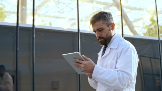 Mature Man Walking with Tablet Computer Medium shot of attentive mature man in lab coat using tablet computer when walking through industrial greenhouse complex hallway, follow shot, side view lab coat stock videos & royalty-free footage