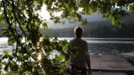 istock Mature man walks onto wooden lake pier at sunrise 1166491421
