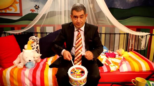 Mature man wearing suit playing toy drum video