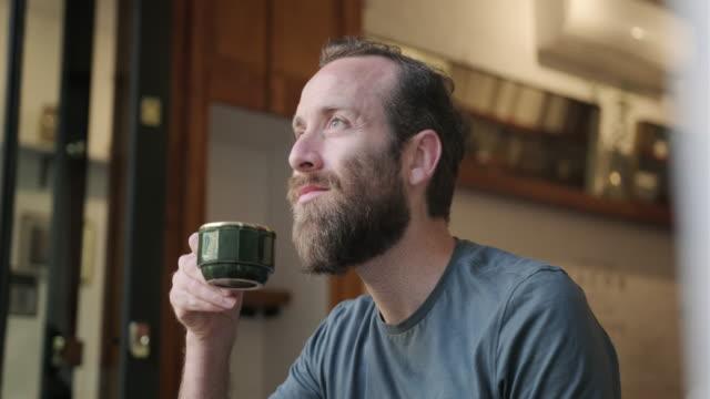 Volwassen man met een baard drinken van een kopje koffie in een cafe video