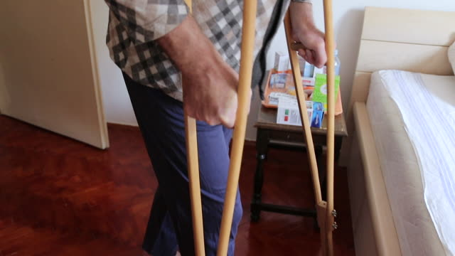 Mature man with crutches going to bed while female nurse assisting him Mature man with crutches going to bed while female nurse assisting him during home visit crutch stock videos & royalty-free footage