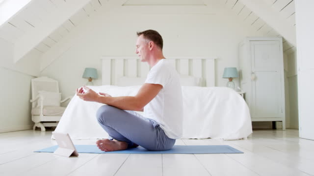 Mature Man With Digital Tablet Sitting In Bedroom Doing Yoga Mature Man With Digital Tablet Sitting In Bedroom Doing Yoga meditating stock videos & royalty-free footage