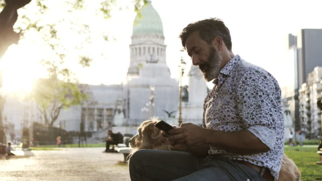 Mature man with golden retriever dog using the phone Mature Latino man with beard any stylish casual clothing in springtime day in Buenos Aires, Argentina. Shot takend with Nikon D850 handsome people stock videos & royalty-free footage