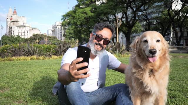 reife mann mit goldenen retriever hund zu fuß im park am nachmittag - fotografieren stock-videos und b-roll-filmmaterial