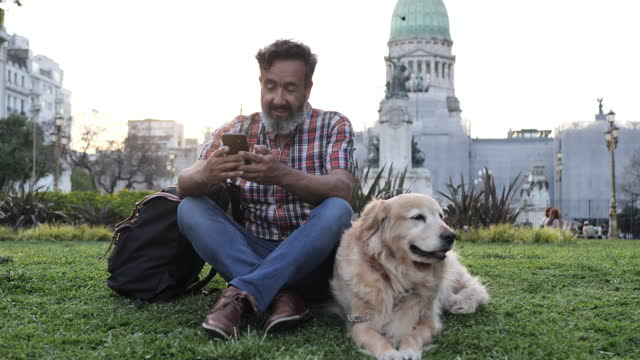 Mature man with golden retriever dog walking in the park in sunset and using phone Mature Latino man with beard any stylish casual clothing in springtime day in Buenos Aires, Argentina. Shot takend with Nikon D850 handsome people stock videos & royalty-free footage
