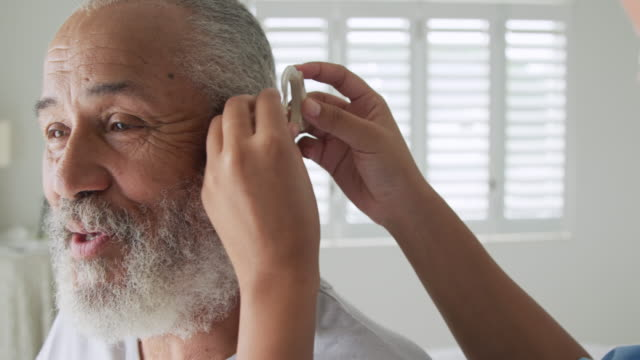 Mature man with hearing aid Front view close up of a mature mixed race man being fitted with a hearing aid mixed race person stock videos & royalty-free footage