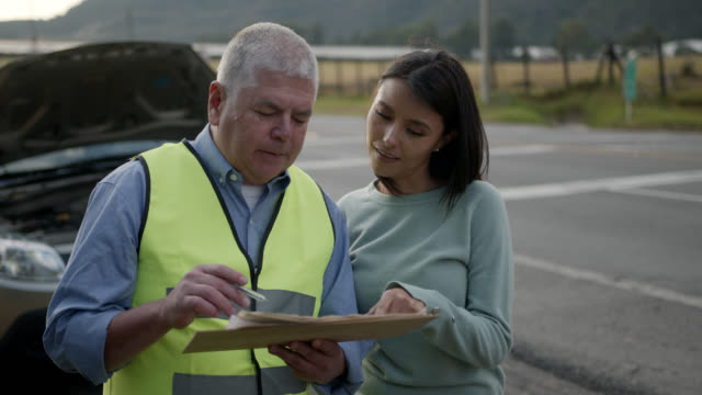 Mature mechanic explaining to female customer everything he wrote on report giving her roadside assistance