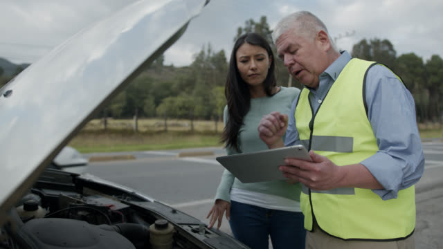 Mature mechanic helping insurance female customer with a vehicle breakdown  holding a tablet