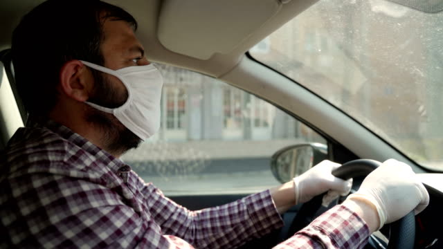 Mature men driving a car with protective mask and protective gloves video
