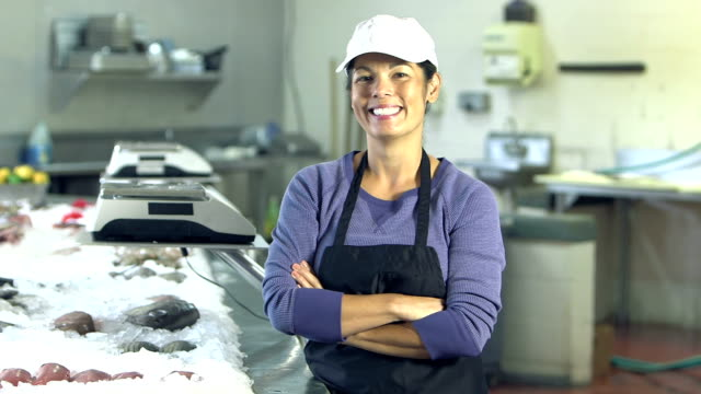 Mature mixed race woman working in fish market - video